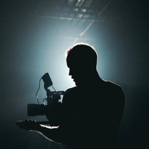 Man holding a camera. Photo by Kyle Loftus.